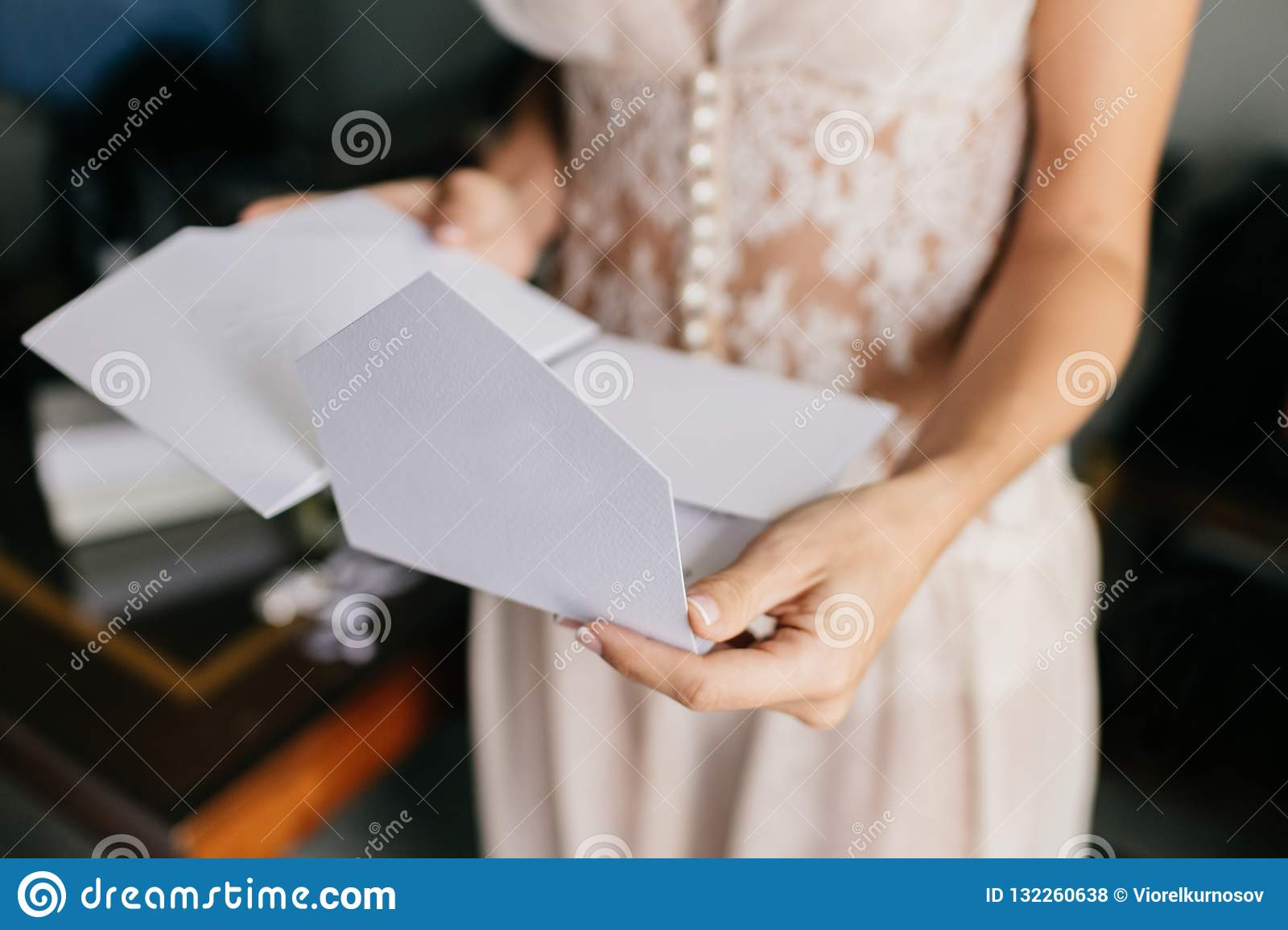Female Bride In White Dress Holds White Letter Or Envelope