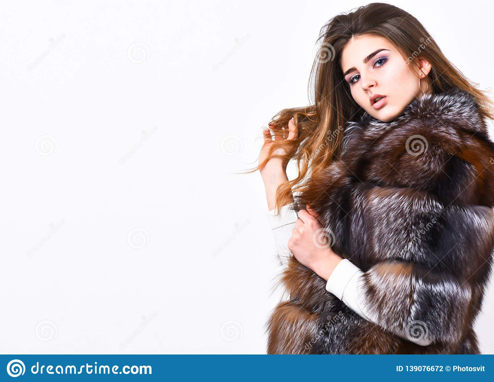 Female brown fur coat. Fur store model enjoy warm in soft fluffy coat with collar. Fur fashion concept. Winter elite