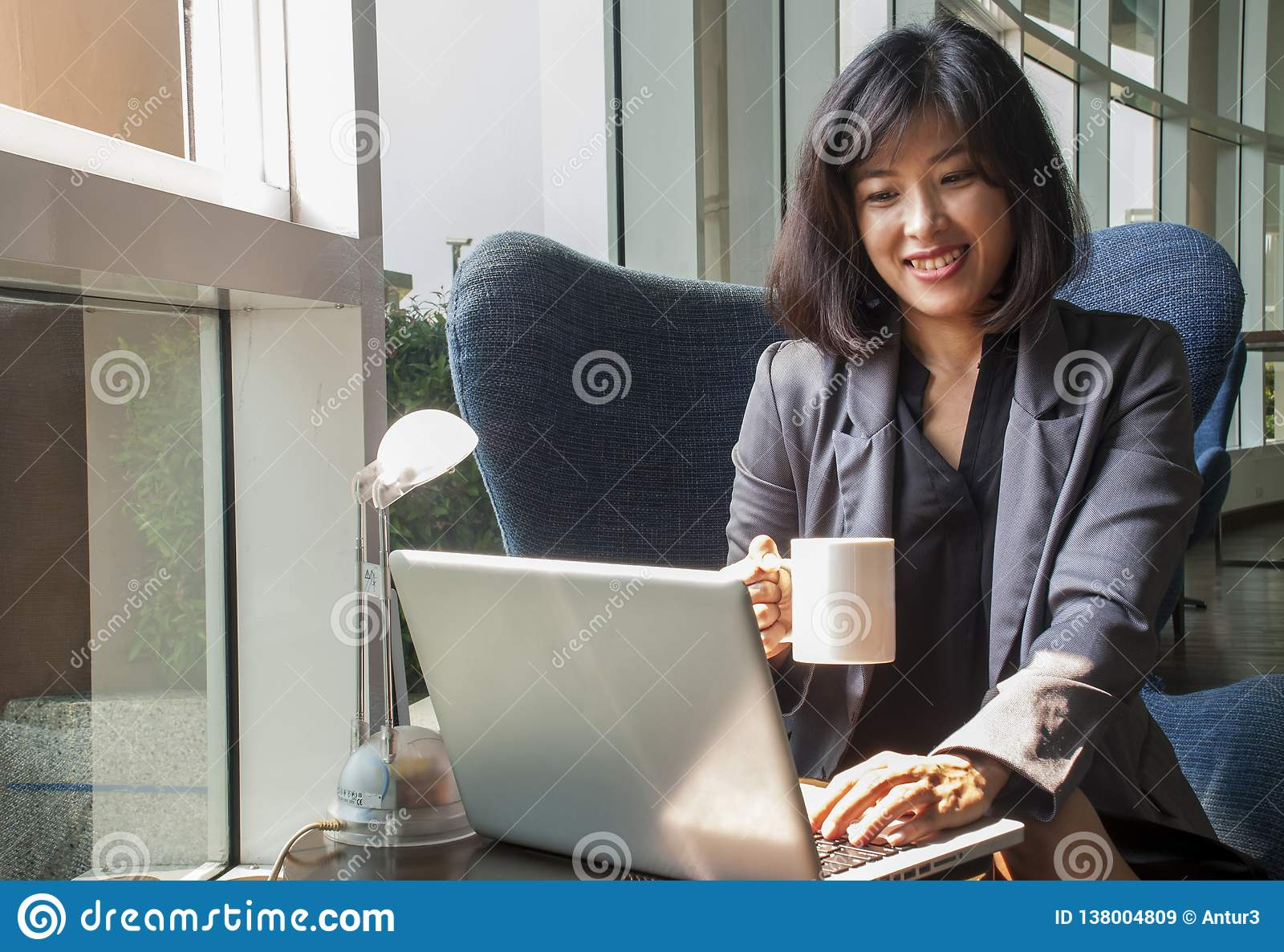 Female businessmen are working on computers and drinking coffee in the office