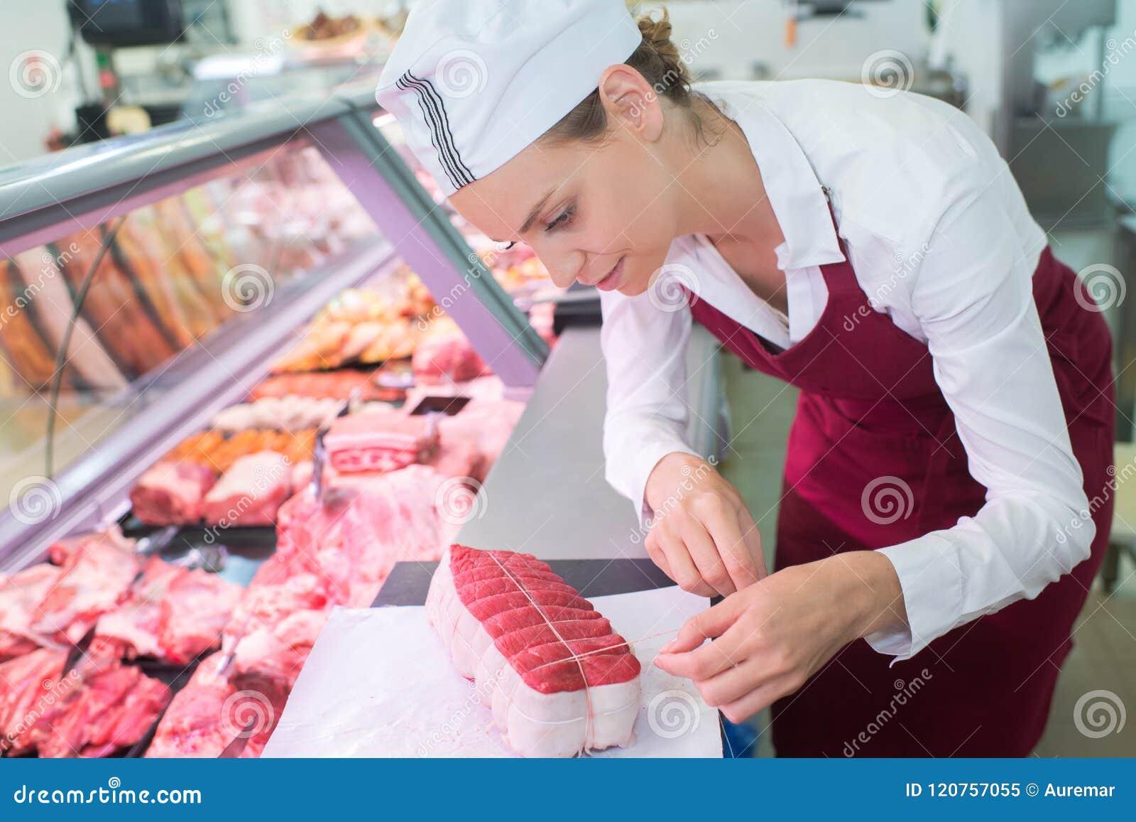 Female butcher preparing filet mignon