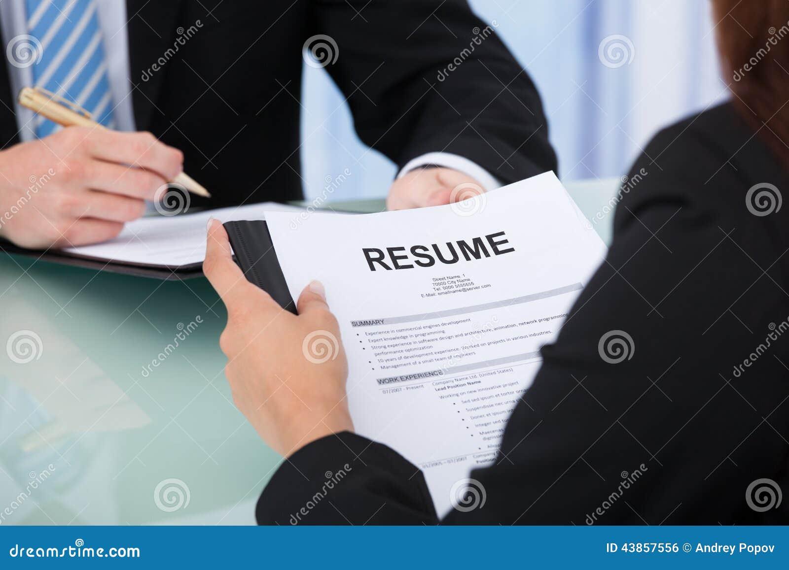 female candidate holding resume at desk stock photo