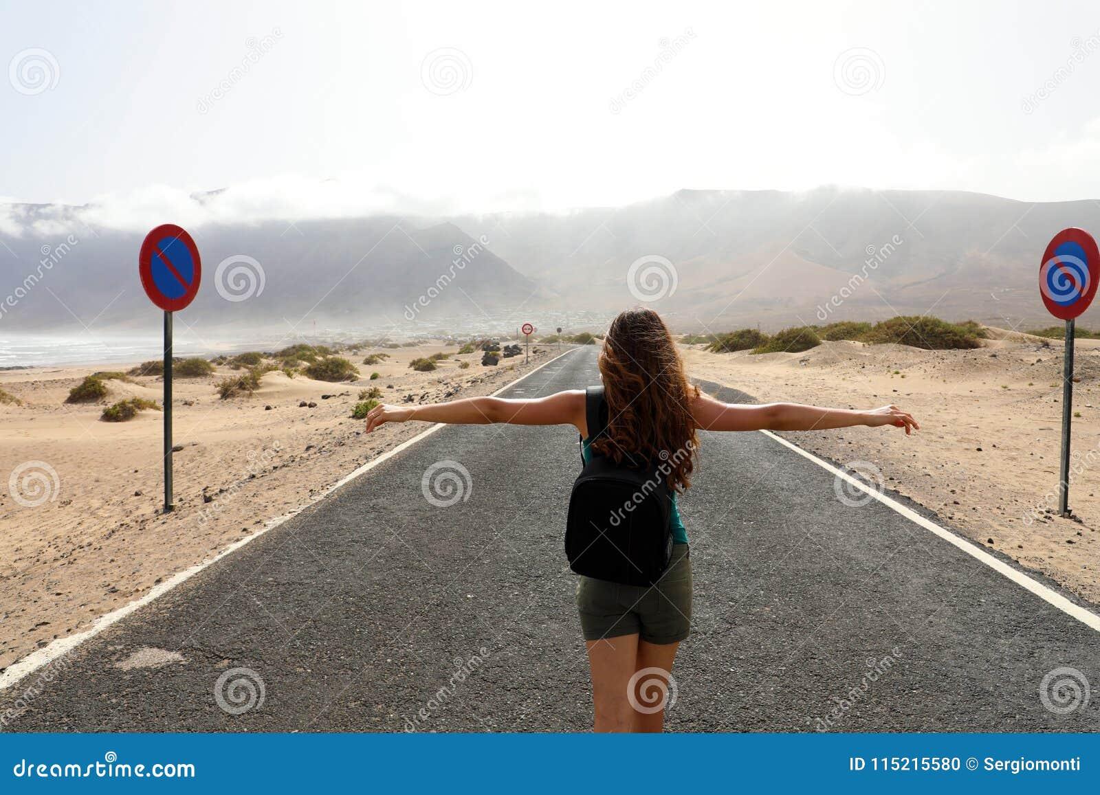 Female carefree backpacker enjoying the landscape in the middle of the desert asphalt road.