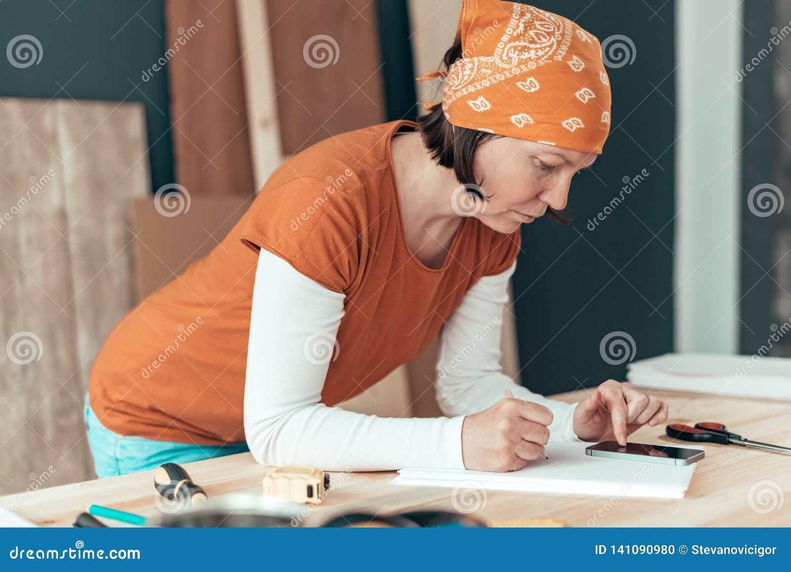Female carpenter doing financial calculation