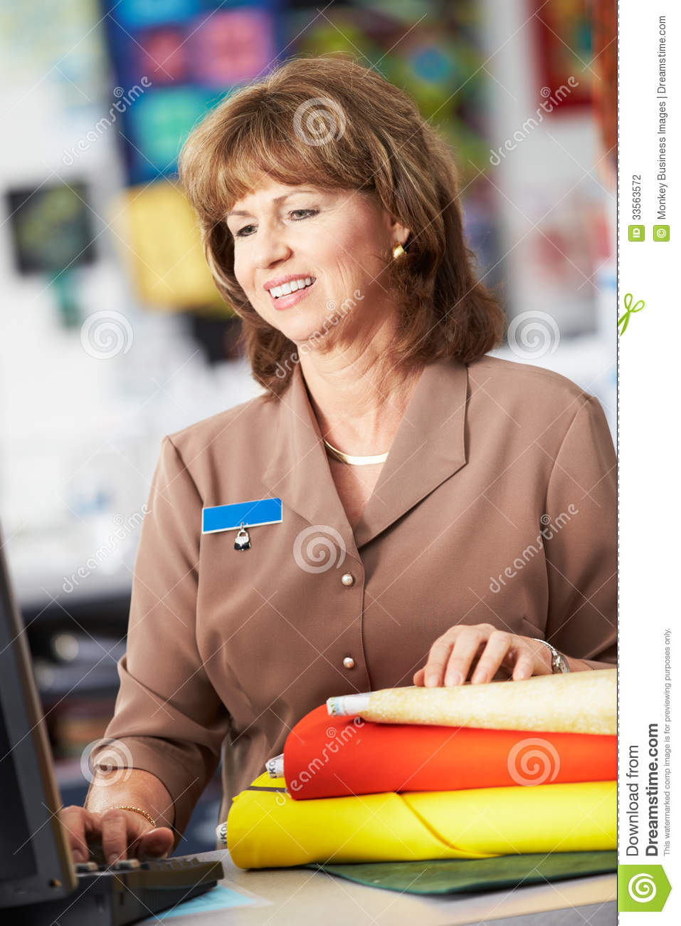 Female Cashier At Clothing Store Working At Computer