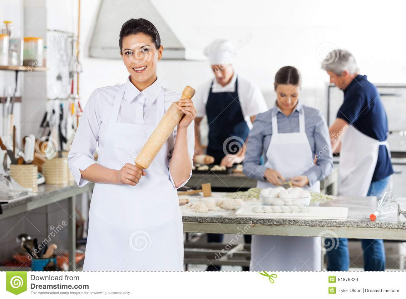 Female Chef Holding Rolling Pin While Colleagues
