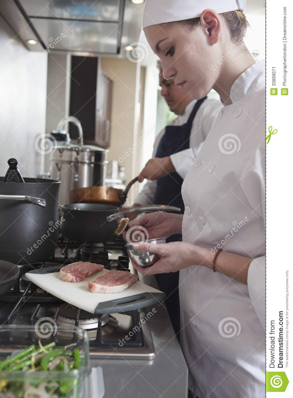 Female Chef Seasoning Raw Meat In Kitchen