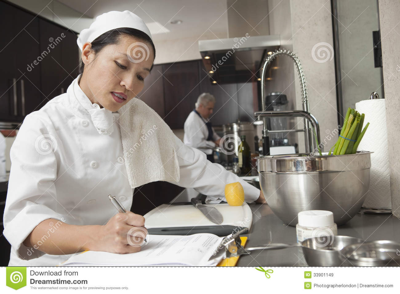 Female Chef Writing On Clipboard In Kitchen