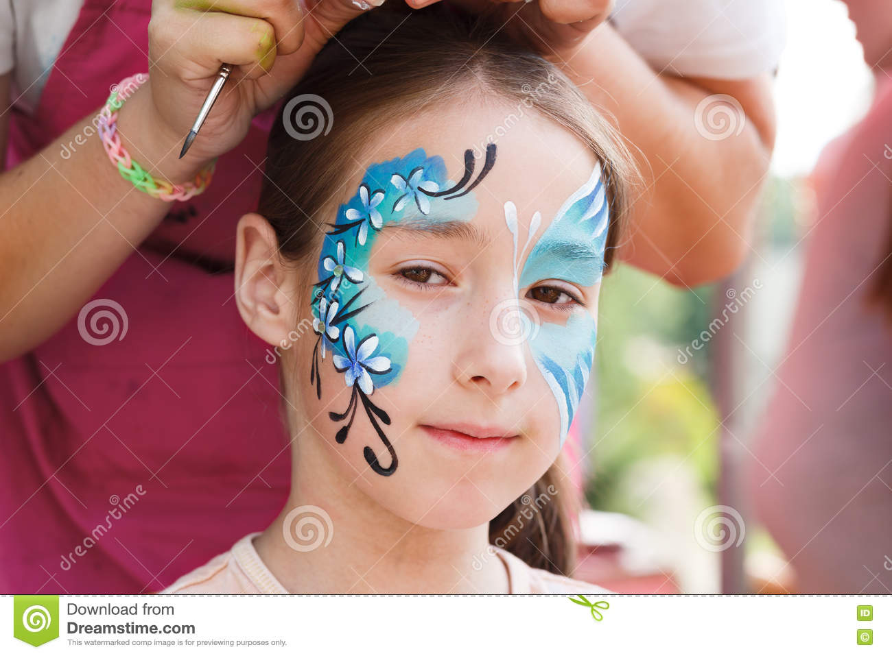 Female child face painting, making butterfly process