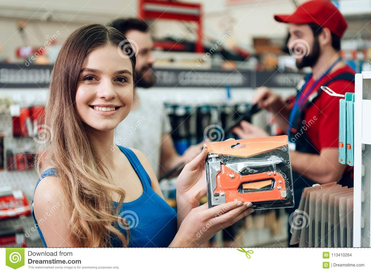 Female client is posing with new stapler in power tools store.