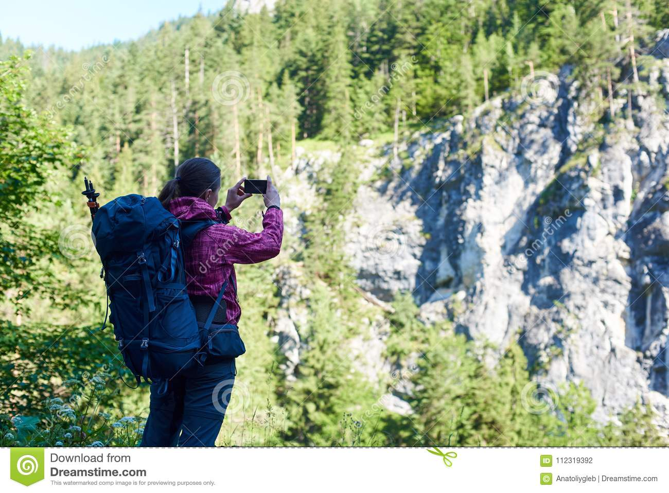 Female climber making picture of spectacular green rock with high trees on top