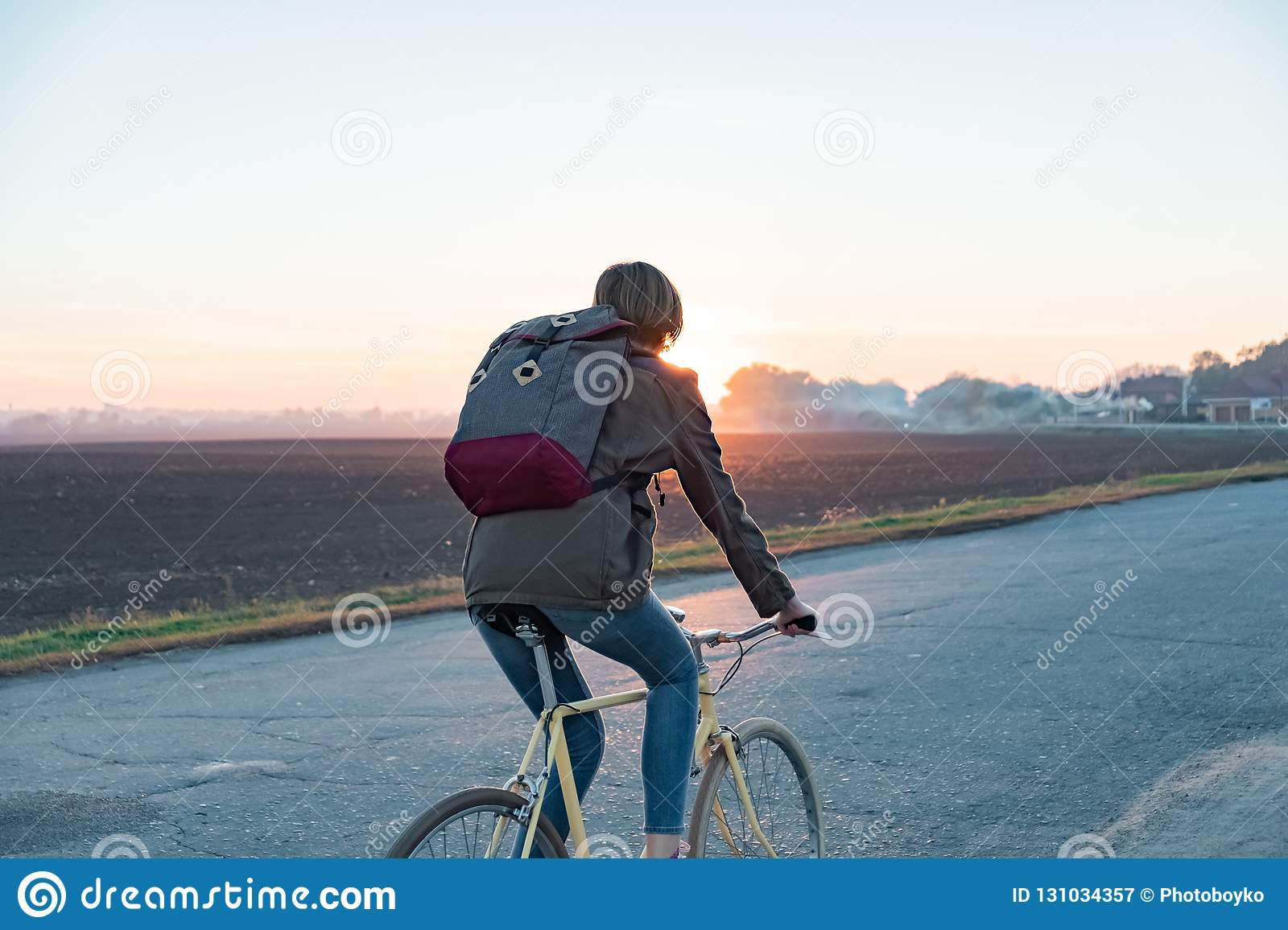 Female commuter riding a bike out of town to a suburban area. Yo