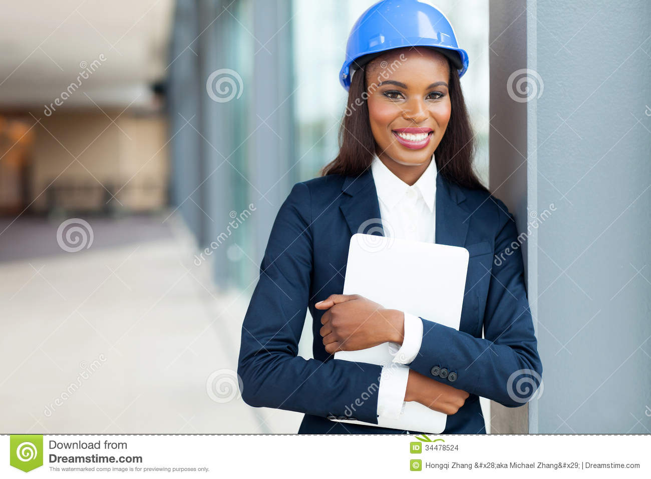 african female construction engineer holding laptop computer