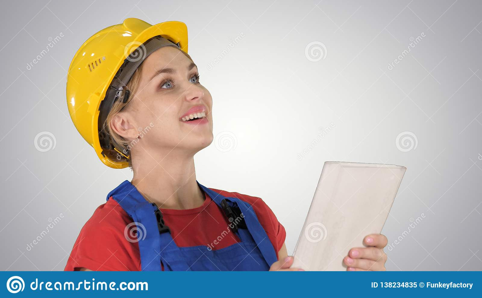 Female construction engineer with a tablet computer at a construction site on gradient background.