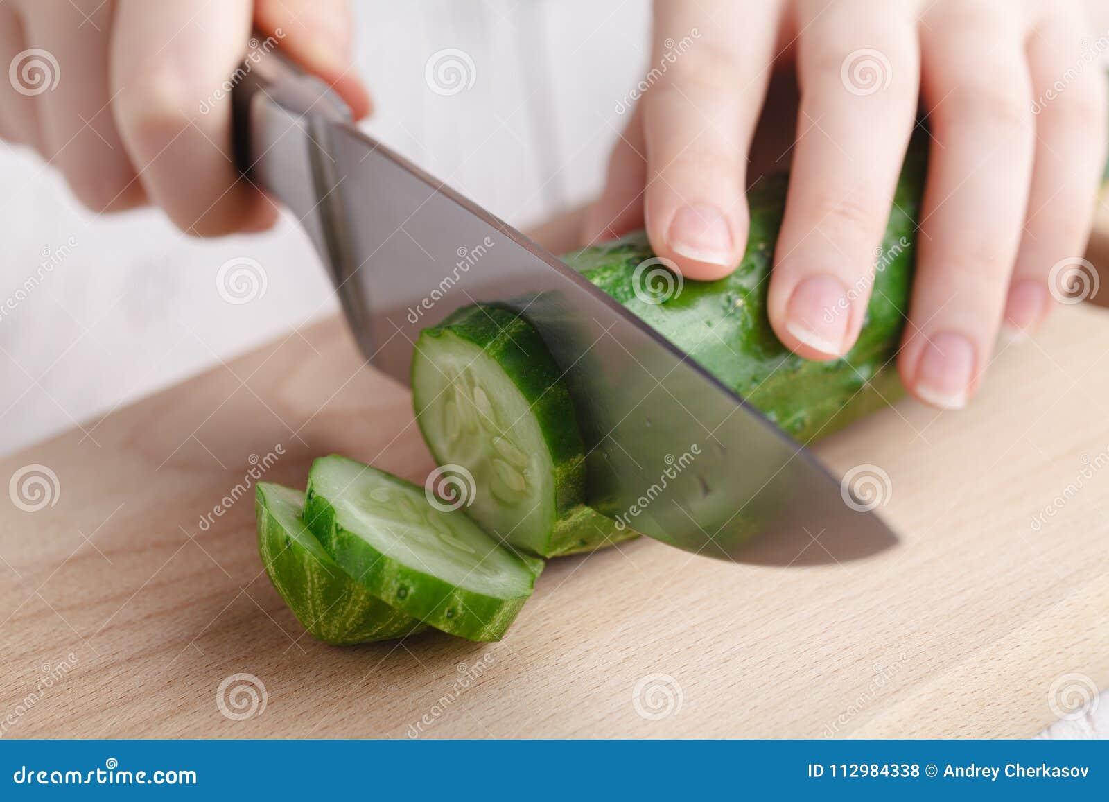 Female cut raw cucumber on cutting board