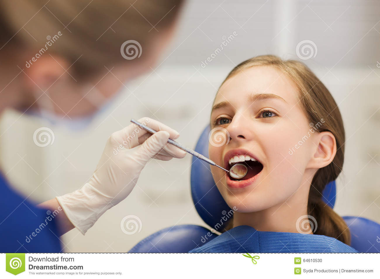 Female dentist checking patient girl teeth