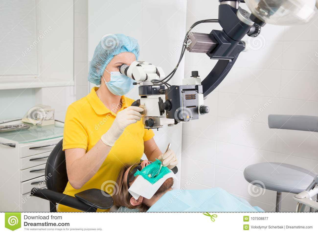 Female dentist with dental tools - microscope, mirror and probe checking up patient teeth at dental clinic office. Medicine, denti