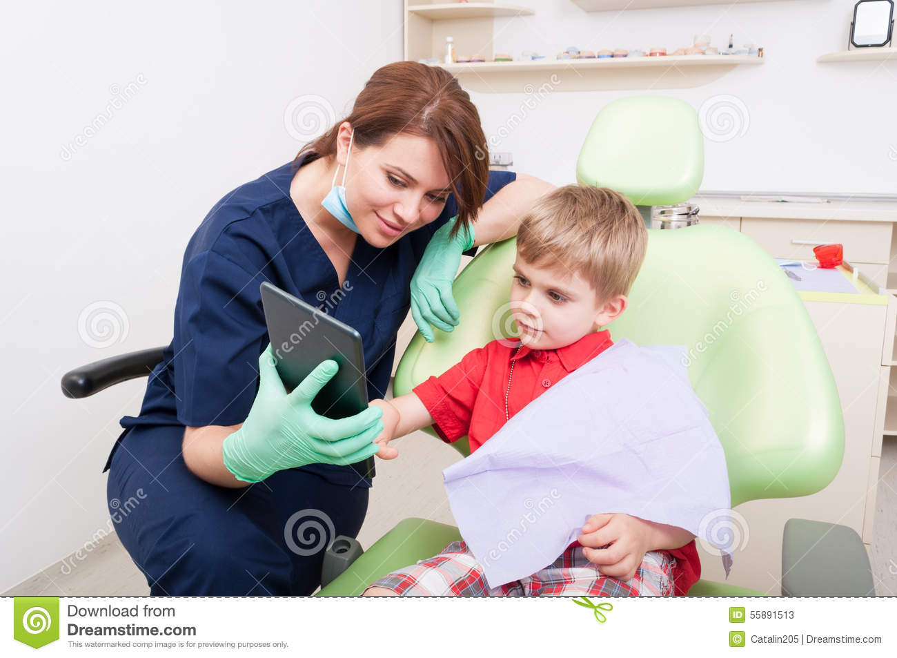 Female dentist using tablet to relax kid patient