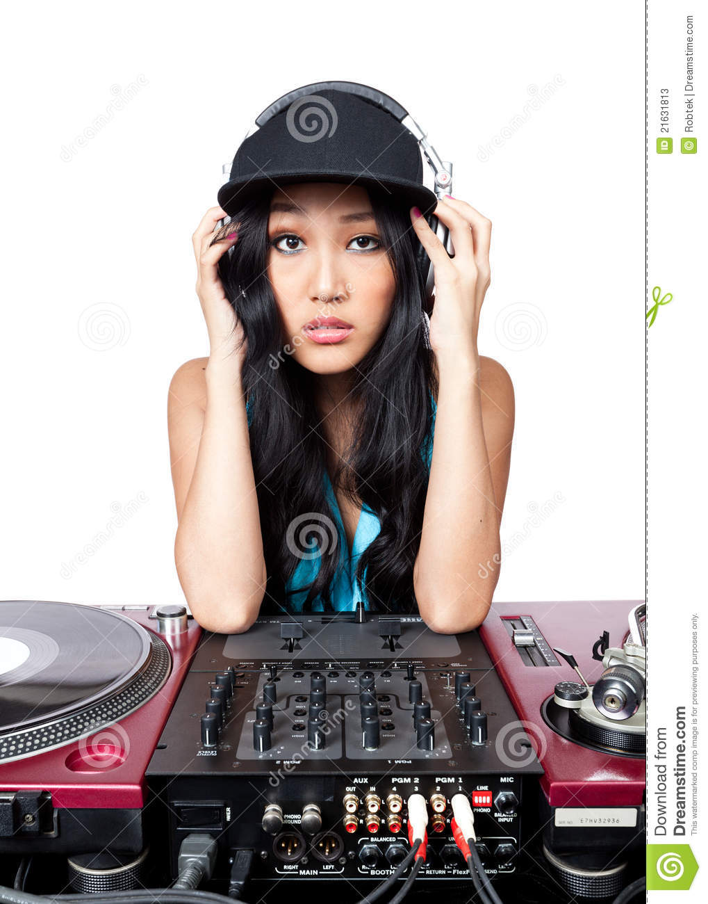 young female Asian DJ posing in for a photo in front of a mixer and ...