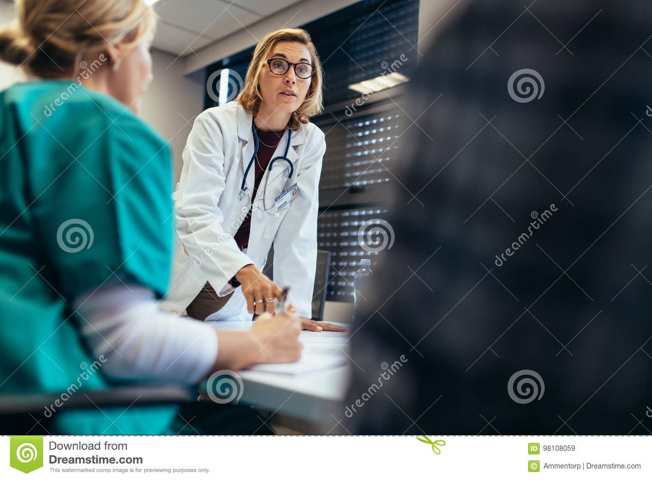 Female doctor briefing her team during meeting