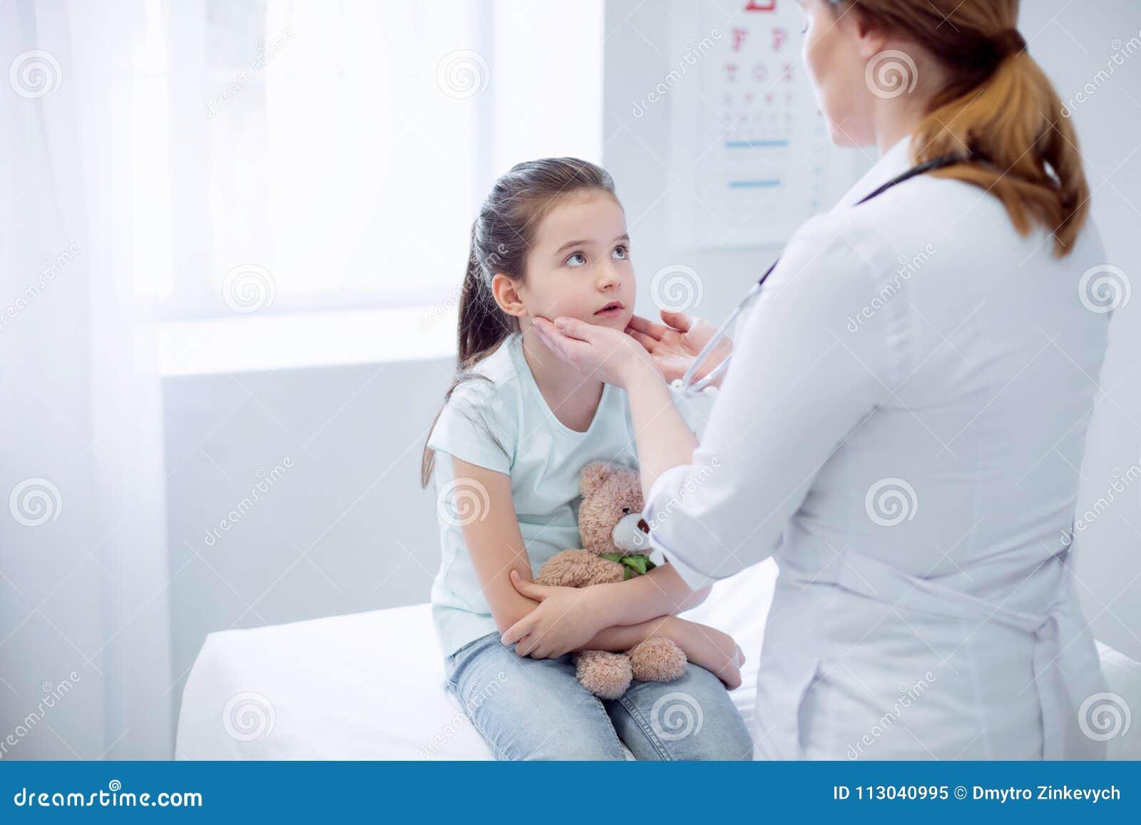 Female doctor checking upset girls tonsils