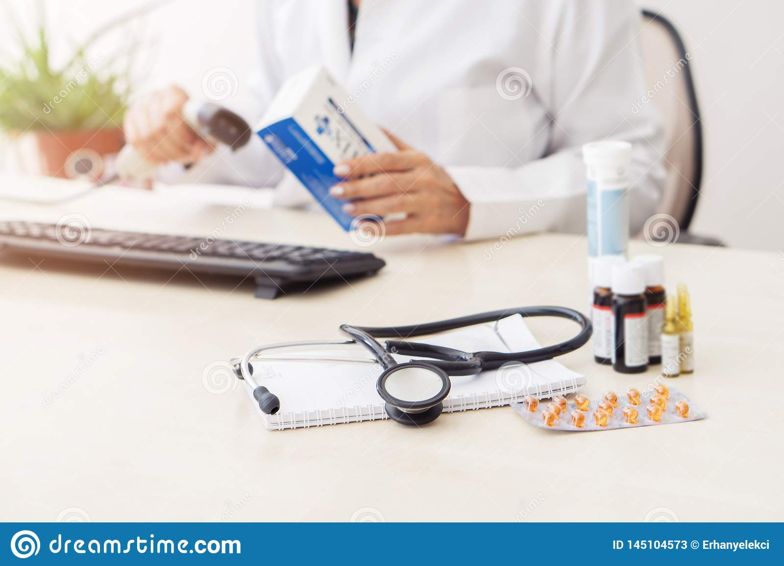 Female doctor entering medication information into computer, there are various drugs on table