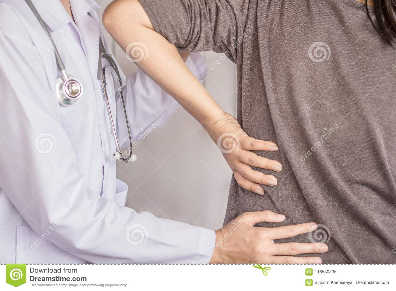 Female doctor examining a patient suffering from back pain