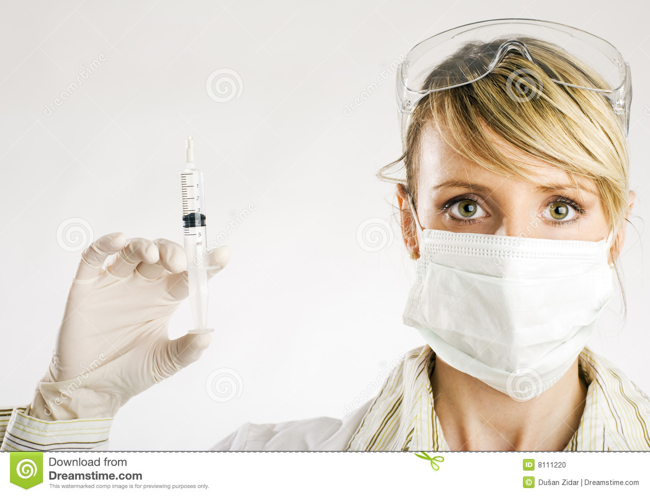 Portrait of young female doctor in face mask holding injection, white