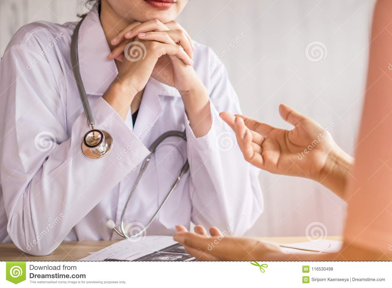 Female doctor listening to depressed patient talking about health problem