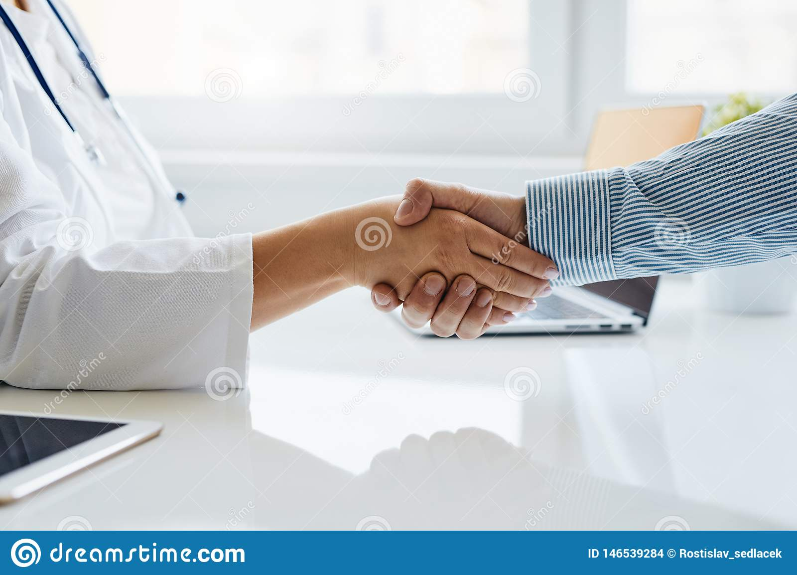 Female doctor shakes hands with his patient