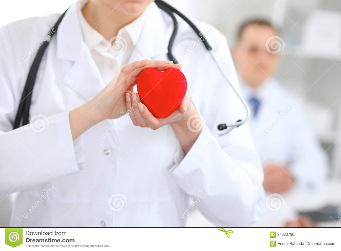 Female doctor with stethoscope holding heart.