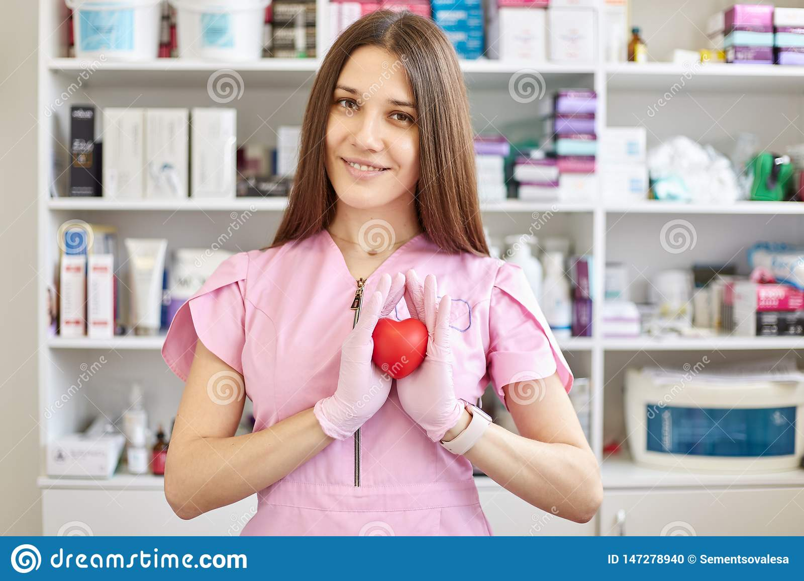 Female doctor wearing pink gown and latex gloves, has long straight brown hair, holds red plastic heart, poses in pharmasy over