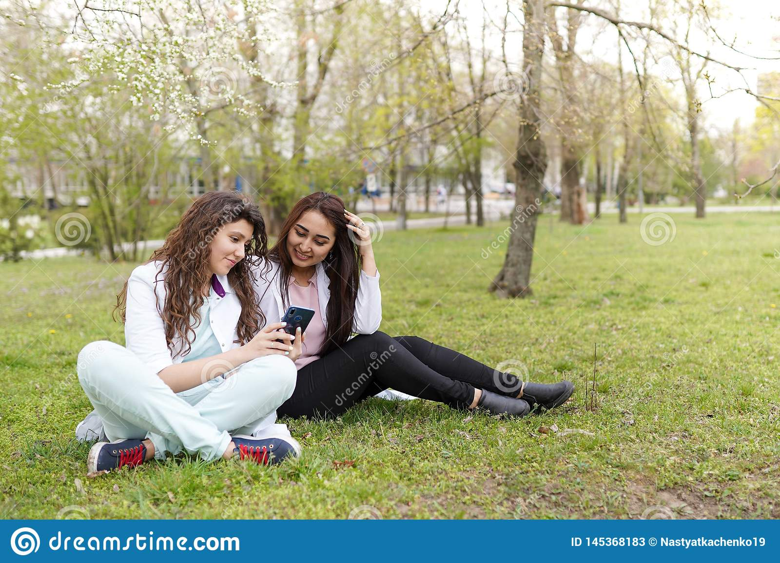 Female doctors student outdoors with phone. medical background . concept of education. students near hospital in flower garden.