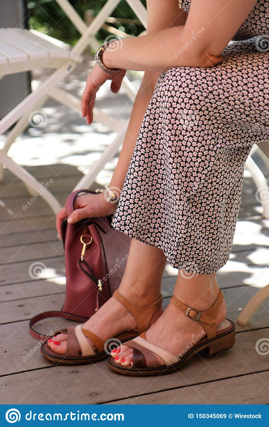 Female in a dress sitting with her hand on her bag