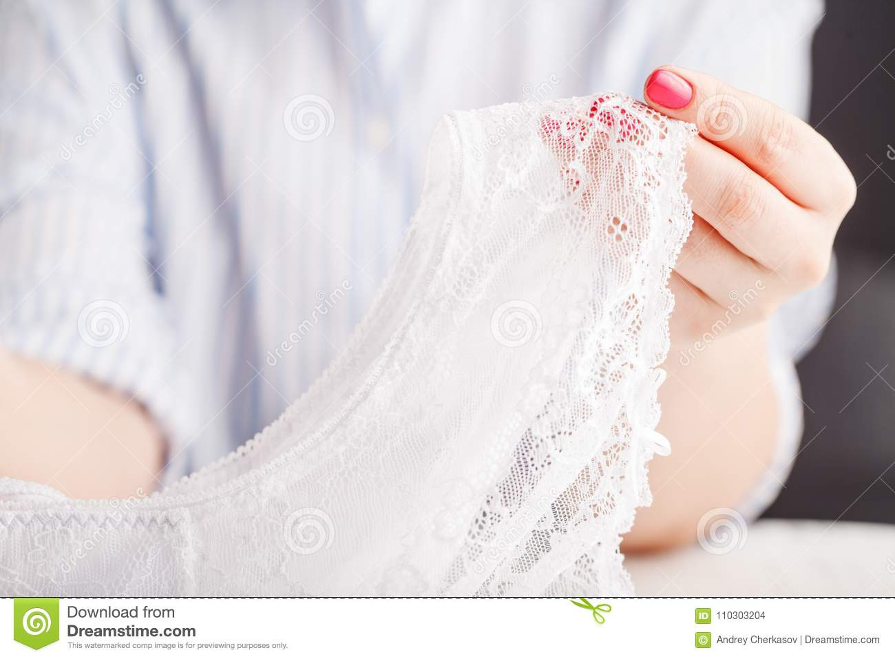 Female erotic fashionable lace panties or lingerie on wooden background with hands