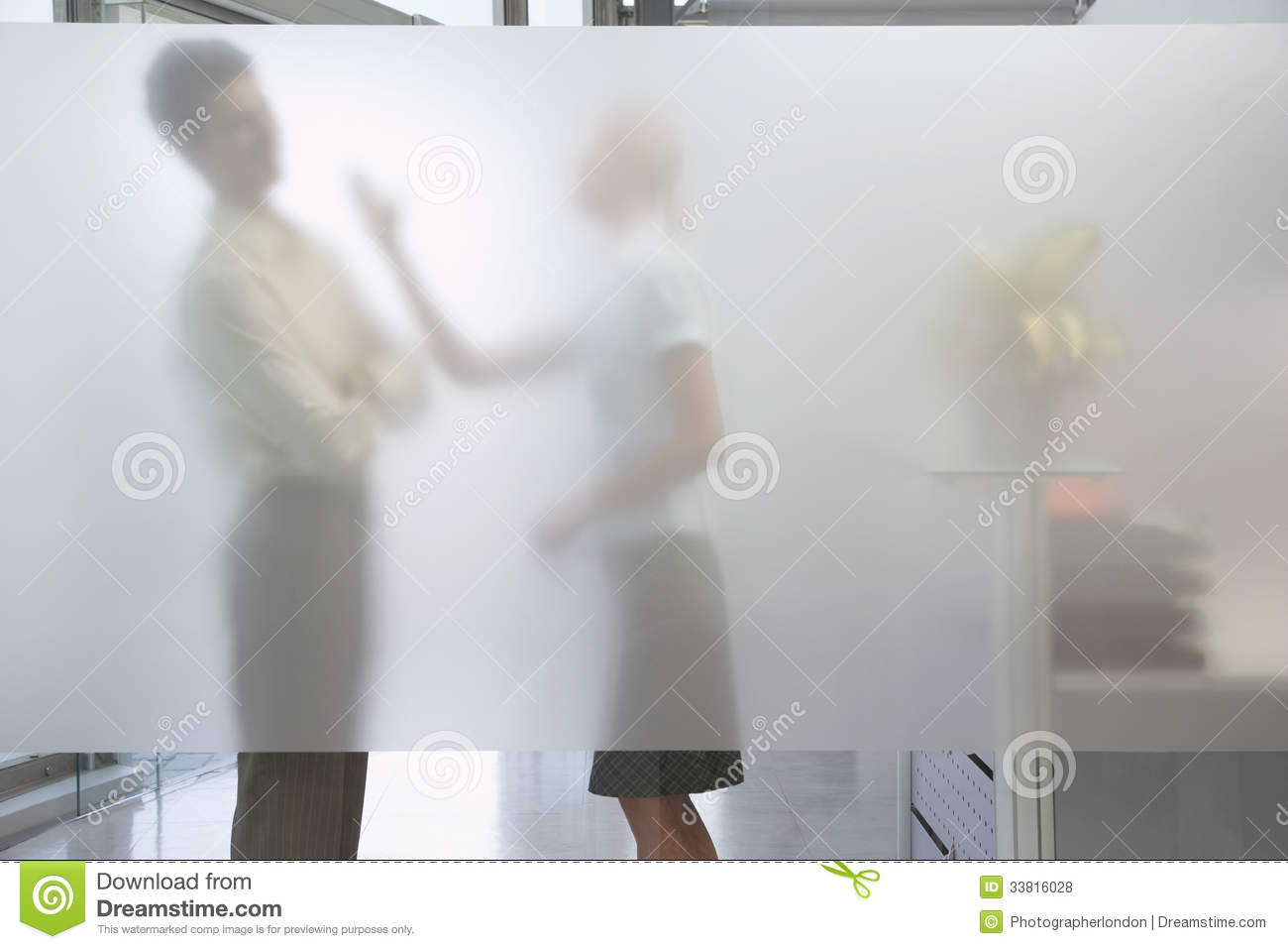 Side view of a female office worker arguing with male colleague behind ...