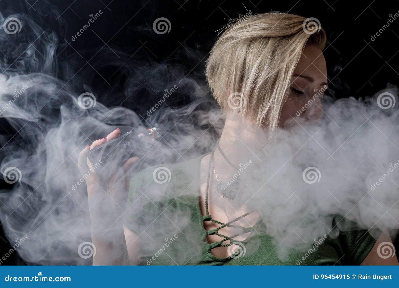 Female exhaling smoke and smoking vaporizer