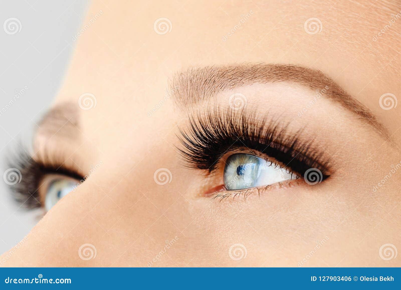 Female eye with extreme long false eyelashes and black liner. Eyelash extensions, make-up, cosmetics, beauty
