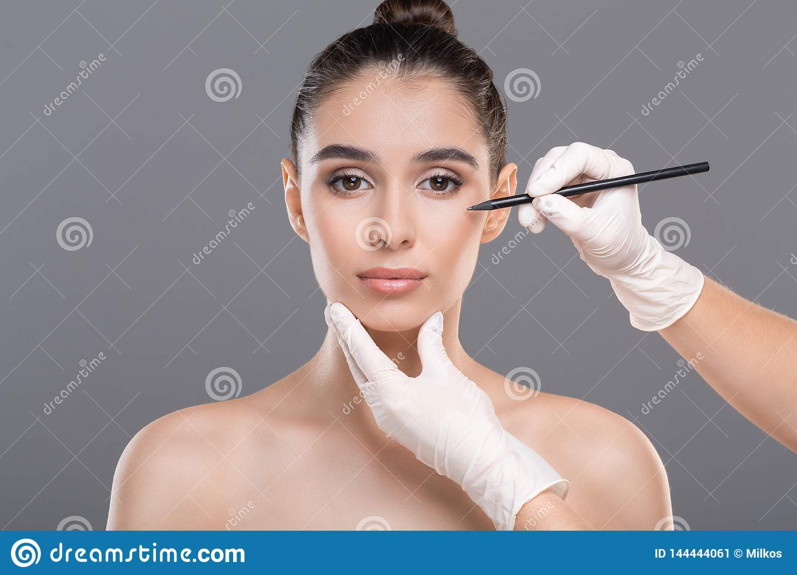 Female face with doctor`s hands with pencil