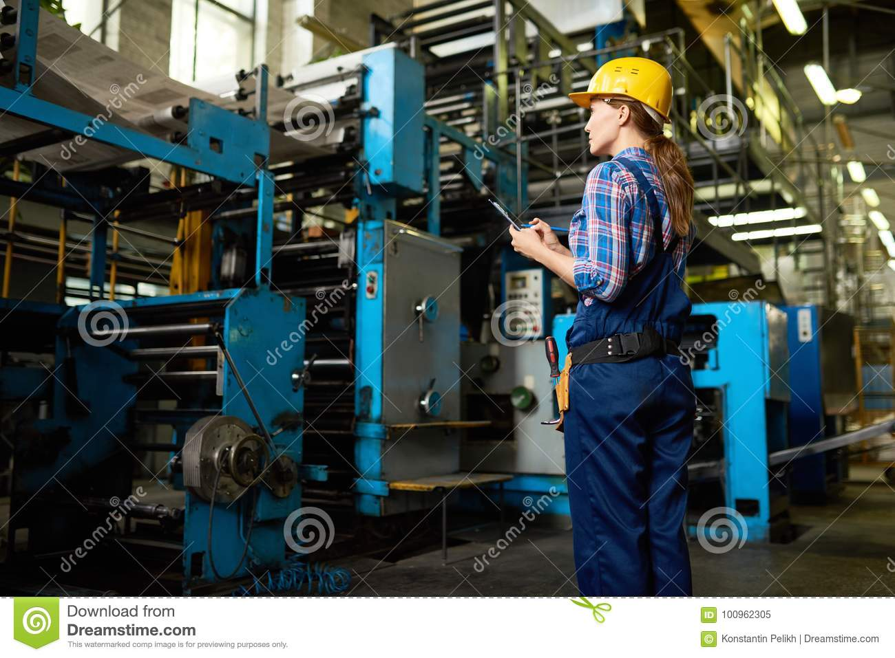 Female Factory Worker Supervising Quality of Production