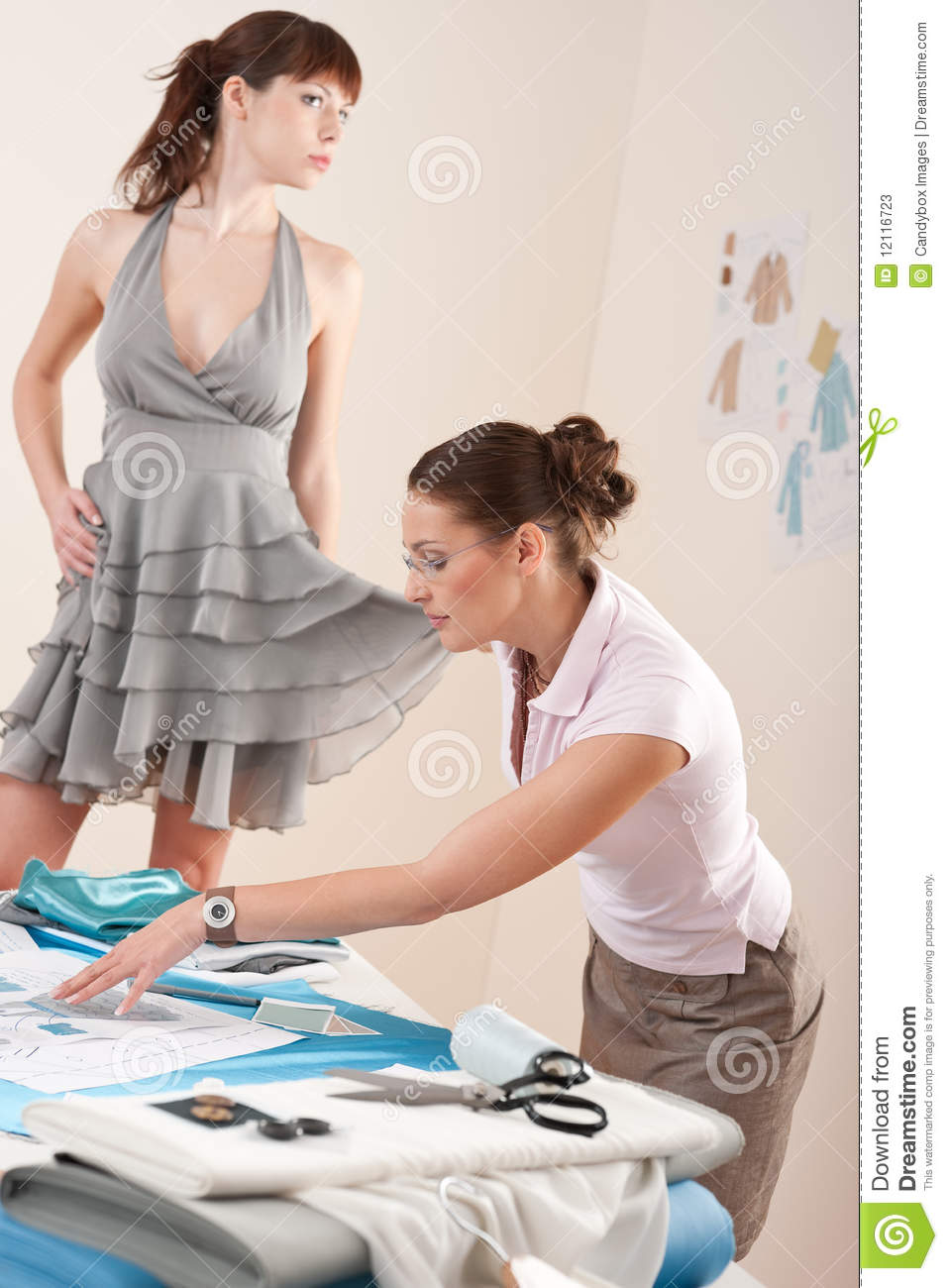 Female Fashion Designer Trying Dress On Model Stock Image