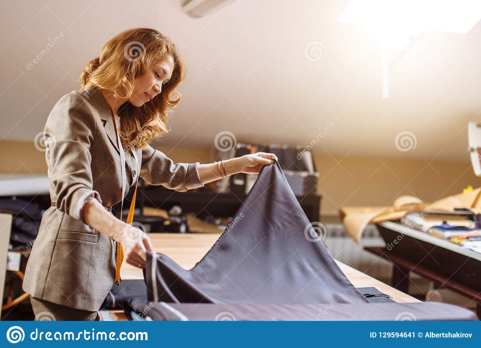 Female fashion designer working on suiting fabric with dressmaking accessories on table