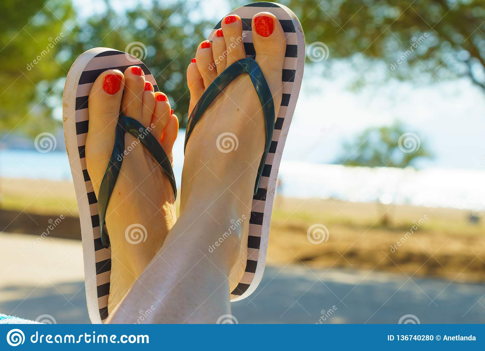 9b70f352fbb82a Unrecognizable woman wearing stripped flip flops and having painted toes  with red nail polish. Female relaxing on beach