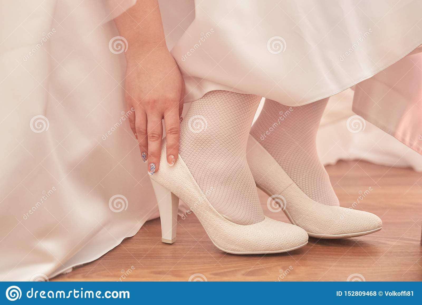 Female feet in white shoes