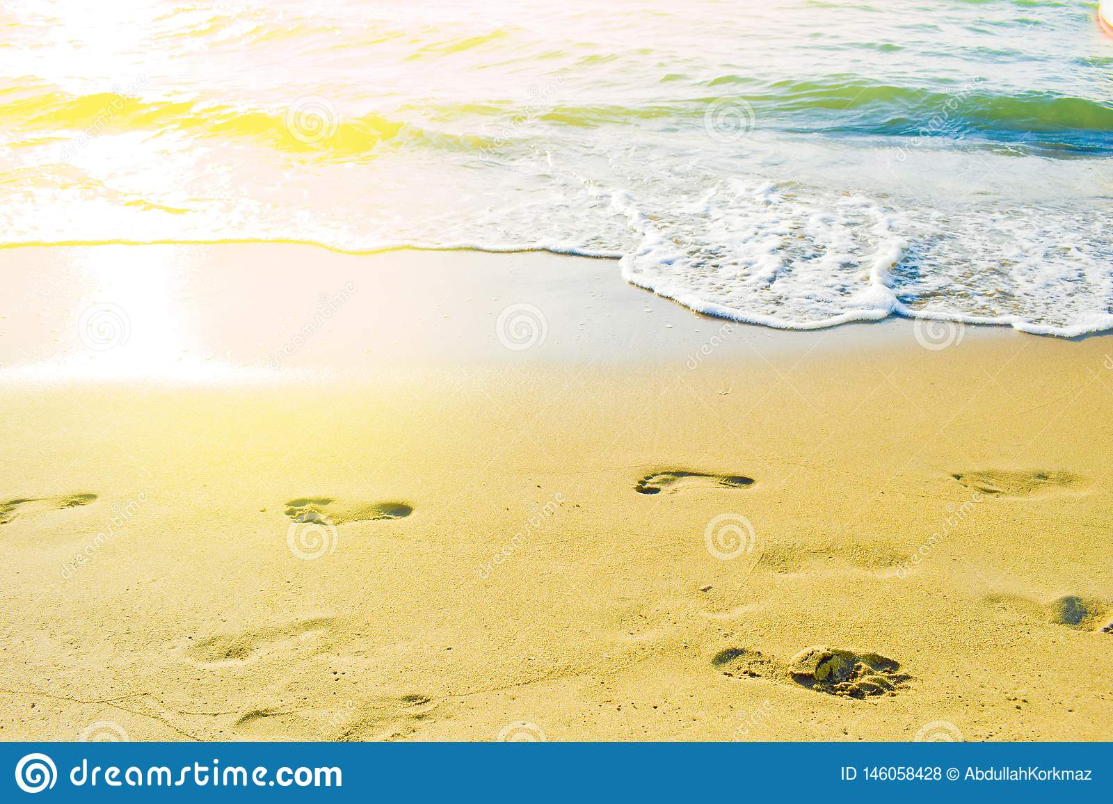 Female footprints on the beach against to sea
