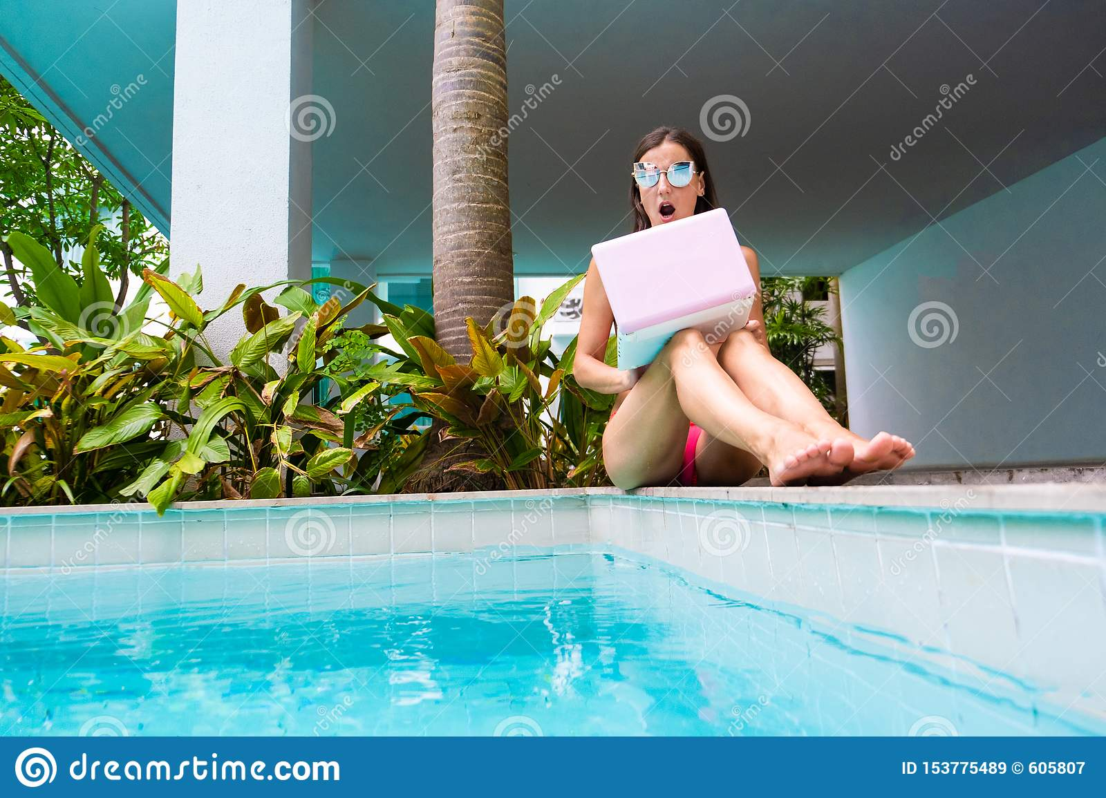 Female freelancer sits by the pool and throws the laptop into the water. girl is outraged, surprised, scared. selective