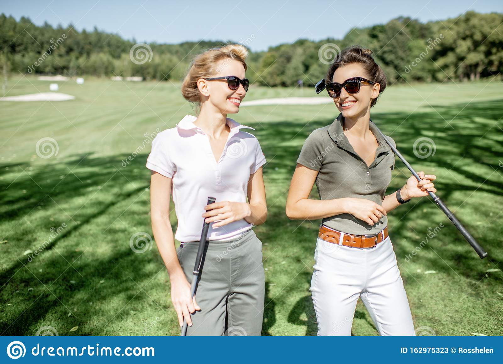 Two Mature Women Kissing On Golf Course Men In Background