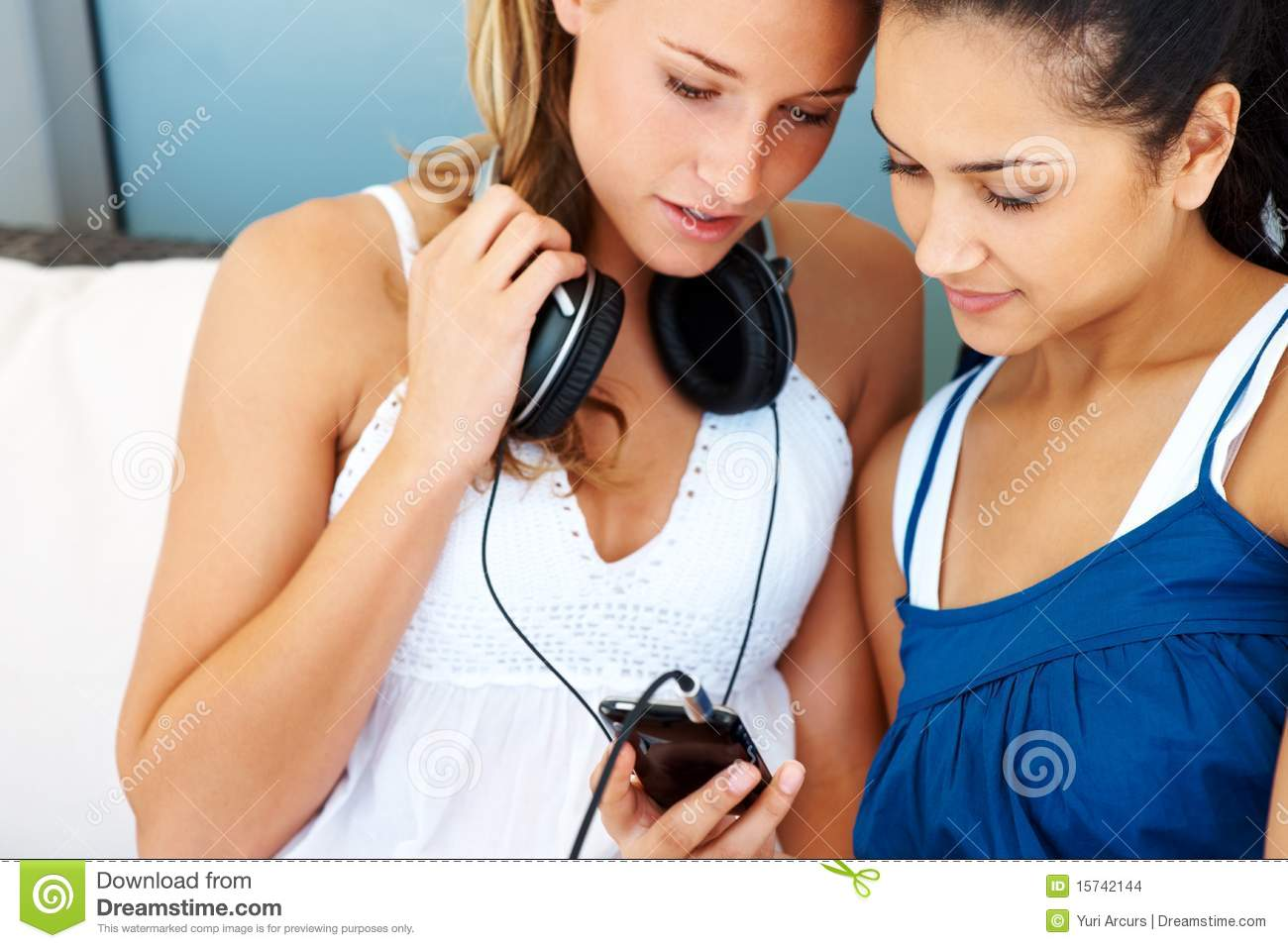 Stock Images: Female friends listening to music on mobile ...