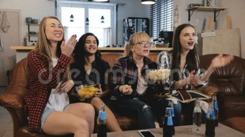 Female friends watch TV show with snacks at home  Young European girls  enjoying romantic comedy slow motion 4K