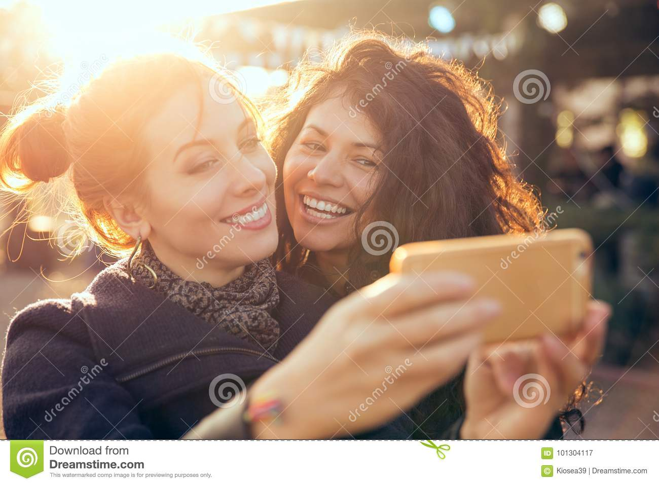 Female friends two women taking selfie during weekend getaway Outdoors
