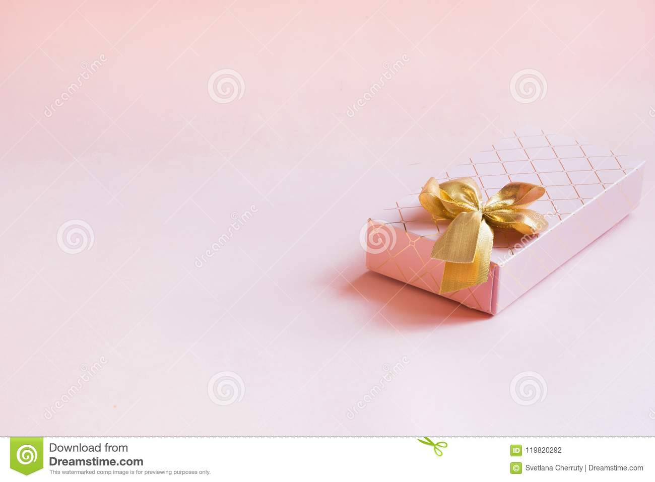 Female gift box with golden ribbon on punchy pastel pink. Birthday. Copy space.